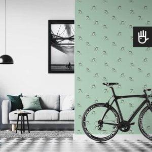 wnętrze mieszkania miłośnika rowerów z miętową tapetą na ścianie z szarymi kolarzami na miętowym tle