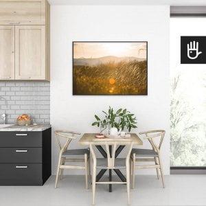 wnętrze kuchni ze stołem nad którym wisi plakat słońce w trawie