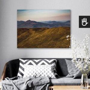 wnętrze salonu z obrazem na płótnie Górskie wędrówki, który wisi na ścianie za kanapą z poduszkami