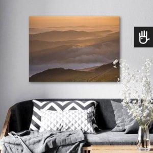 wnętrze salonu z obrazem na płótnie Tajemnicze Bieszczady, który wisi na ścianie za kanapą z poduszkami