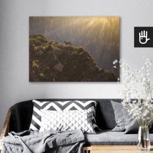 wnętrze salonu z obrazem na płótnie Kozice górskie, który wisi na ścianie za kanapą z poduszkami