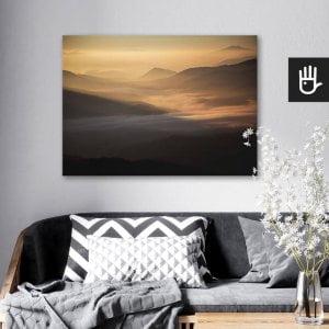wnętrze salonu z obrazem na płótnie przełęcz w słońcu, który wisi na ścianie za kanapą z poduszkami