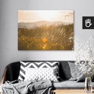 wnętrze salonu z obrazem na płótnie Słońce w trawie, który wisi na ścianie za kanapą z poduszkami