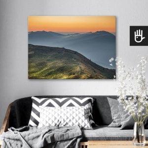 wnętrze salonu z obrazem na płótnie Wschód w Bieszczadach, który wisi na ścianie za kanapą z poduszkami