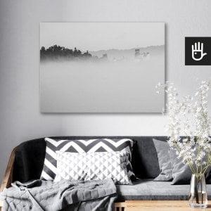 wnętrze salonu z obrazem na płótnie Zamek we mgle, który wisi na ścianie za kanapą z poduszkami