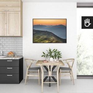 wnętrze kuchni ze stołem nad którym wisi plakat Wschód w Bieszczadach