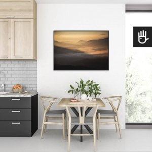 wnętrze kuchni ze stołem nad którym wisi plakat Przełęcz w słońcu