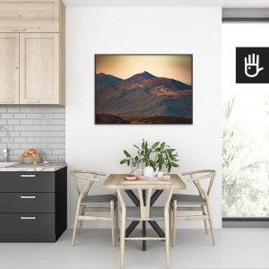 wnętrze kuchni ze stołem nad którym wisi plakat Połonina Wetlińska