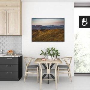 wnętrze kuchni ze stołem nad którym wisi plakat Górskie wędrówki