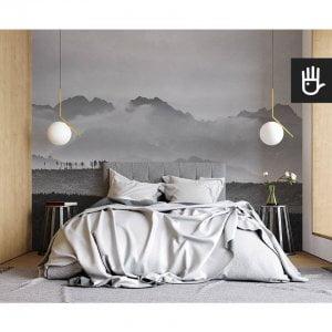 nowoczesna sypialnia w stylu naturalnym z fototapetą Szczyty w chmurach na ścianie za łóżkiem