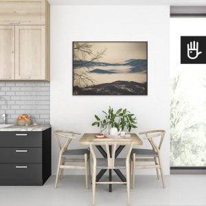 wnętrze kuchni ze stołem nad którym wisi plakat Beskidy we mgle