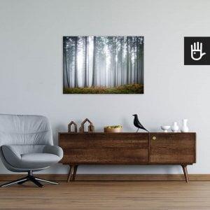 Wnętrze salonu w stylu loft z fotelem, komodą i obrazem na ścianie z Tajemniczym mglistym lasem