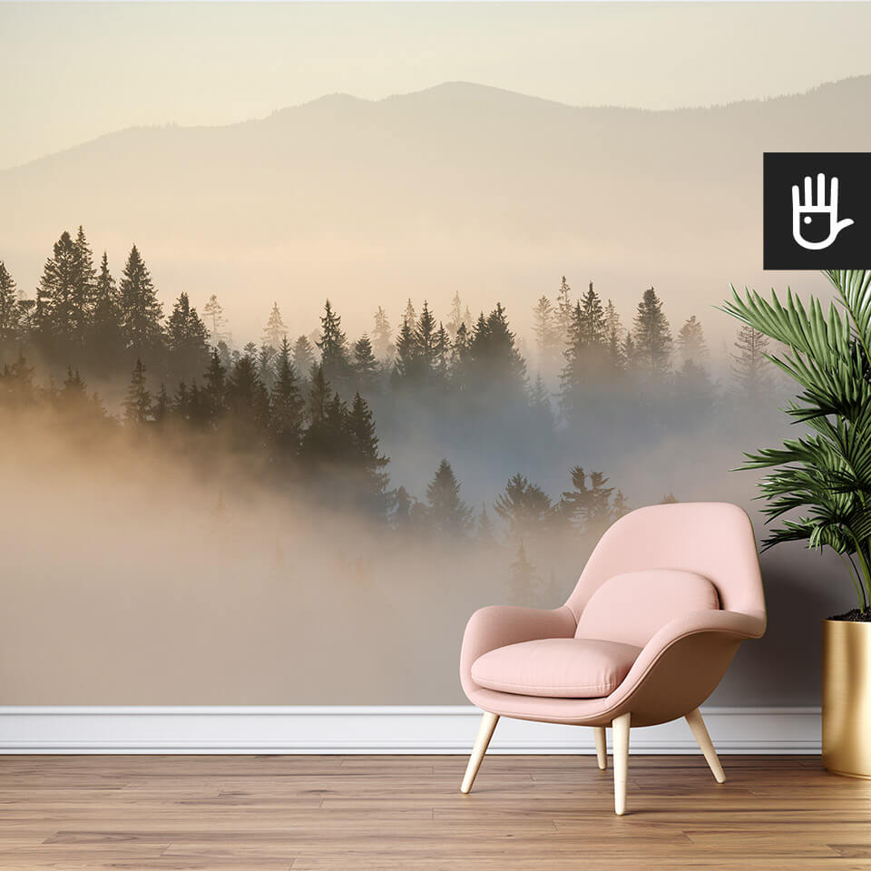 salon z różowym fotelem na tle ściany z fototapetą wschód słońca nad lasem