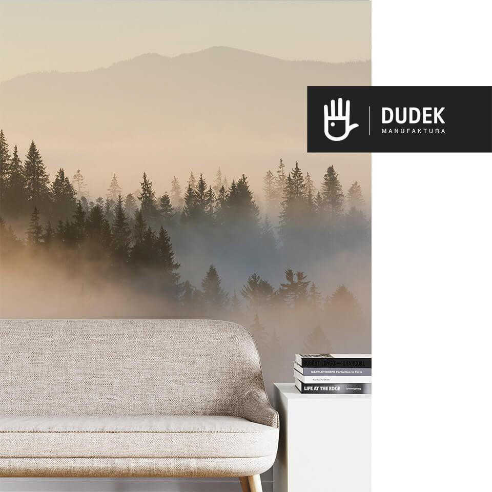 Fragment wnętrza pokoju z beżową kanapą na tle fototapety ze wschodem słońca nad lasem