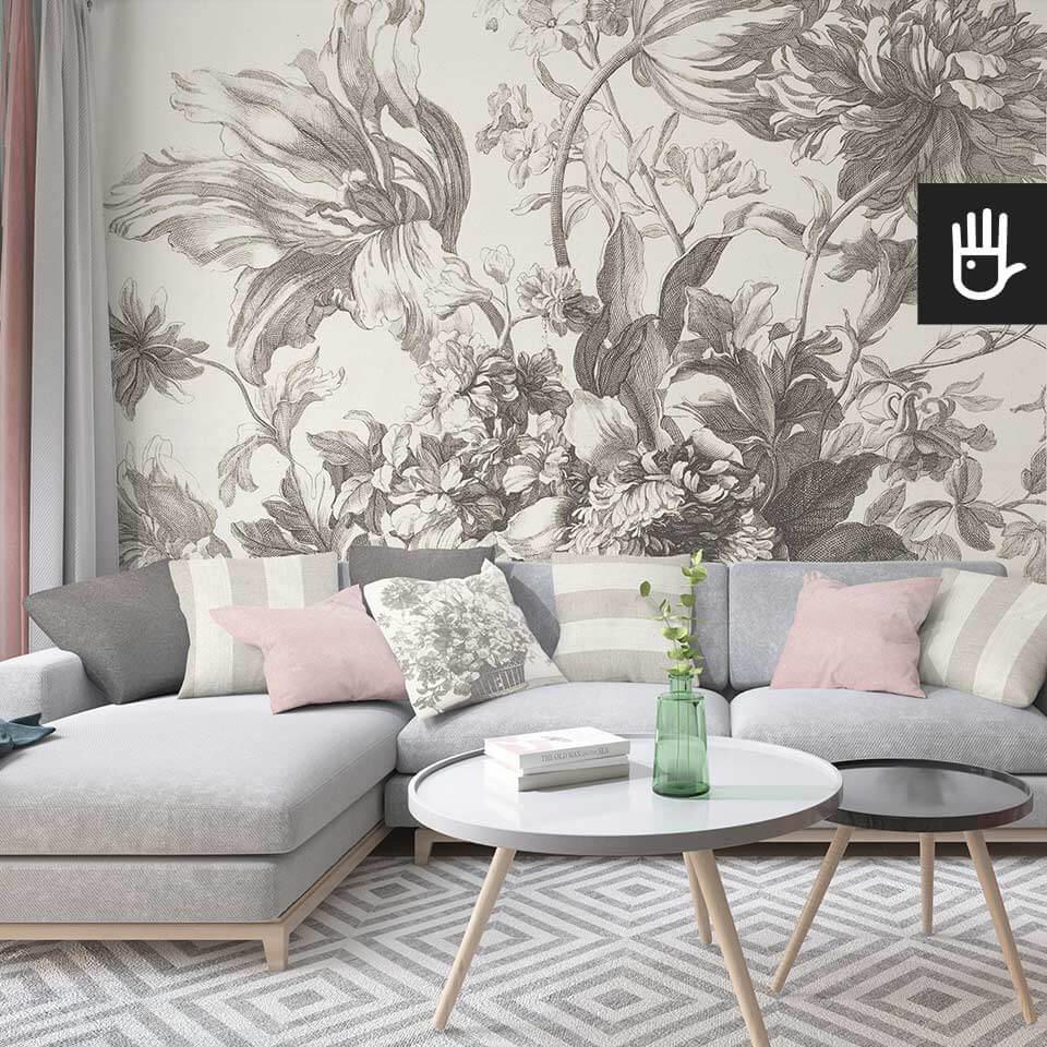 Salon z szarą narożną kanapą na tle kwiatowej tapety