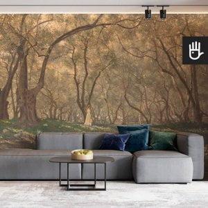Wnętrze stylowego salonu z szarą kanapą na tle ściany z fototapetą pod oliwnymi drzewami z lasem w słońcu