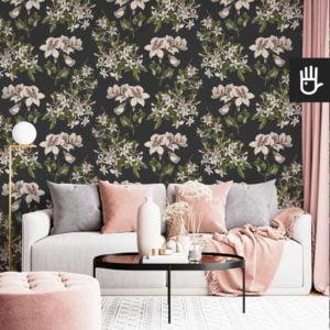 Stylowy salon z białą kanapą i dodatkami w kolorze pudrowego różu z kwiatową tapetą ścienną z kwiatami azalii i pelargoniiii