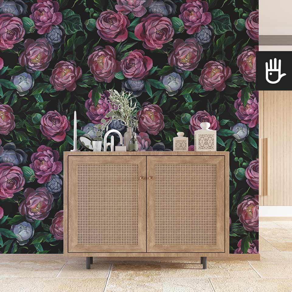Przedpokój z drewnianą komodą w stylu boho na tle ściany z tapetą w fioletowe piwonie z zielonymi liśćmi.
