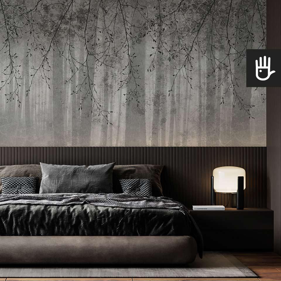 Nastrojowa sypialnia z ciemnym łóżkiem na tle fototapety echo lasu w szarej kolorystyce z motywem gałęzi